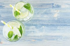 Free Fresh Cold Summer Beverage Mojito With Lime, Leaf Mint, Straw, Ice Cubes, Soda On Blue Wood Background, Top View, Border. Royalty Free Stock Images - 114677949
