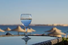 Fresh cold water in a glass with a straw on the table at sea. Summer holiday vacation concept. stock photography