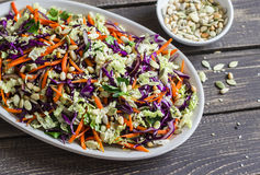 Fresh Cole slaw with pumpkin, flax, sesame seeds and pine nuts - delicious healthy vegetarian food. On a dark rustic wooden background Stock Images