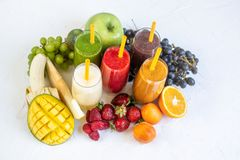 Fresh Color Juices Smoothie Green Yellow Red Orange Violet White Tropical Fruits. Mango Melon Kiwi Strawberry Banana Peaches Grapes Glass White Background royalty free stock photography