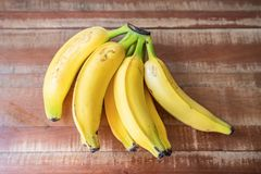 Fresh and colorful bananas on wooden background royalty free stock photo