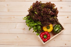 Fresh colorful bell pepper box on wooden table. Top view Royalty Free Stock Photos