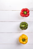 Fresh colorful bell pepper box on wooden table. Top view Royalty Free Stock Photo