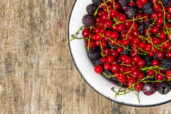 Fresh colorful berries in bowl on rustic wooden table Stock Photography