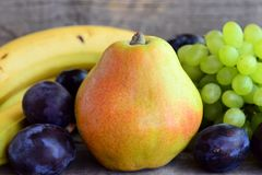 Fresh colorful fruits assortment. Fresh raw pear, grapes, blue plums, bananas on a wooden table. Closeup Royalty Free Stock Image