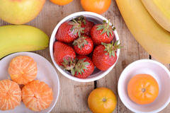 Fresh colorful fruits composition mandarin, strawberry, peach, bananas and orange Royalty Free Stock Photos