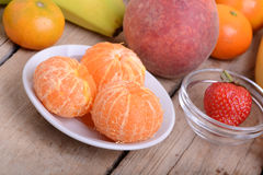 Fresh colorful fruits composition mandarin, strawberry, peach, bananas and orange Royalty Free Stock Images