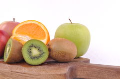 Fresh colorful fruits macro. Fresh fruits on wooden plate  on white backgorund Royalty Free Stock Images