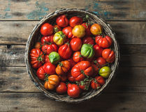 Fresh colorful ripe heirloom tomatoes in basket over wooden background Royalty Free Stock Image