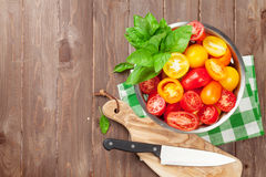 Fresh colorful tomatoes and basil in colander Stock Image