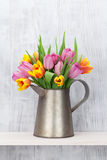 Fresh colorful tulip flowers bouquet. On shelf in front of wooden wall Stock Photos