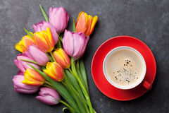 Fresh colorful tulip flowers and coffee. Cup on dark stone table. Top view Stock Photography