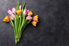 Fresh colorful tulip flowers. On dark stone table. Top view with copy space Royalty Free Stock Image