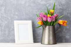 Fresh colorful tulips bouquet and photo frame. Fresh colorful tulip flowers bouquet and blank photo frame with copy space on shelf in front of stone wall Royalty Free Stock Photos