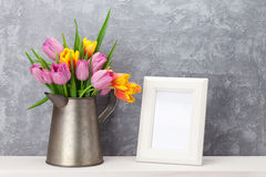 Fresh colorful tulips bouquet and photo frame. Fresh colorful tulip flowers bouquet and blank photo frame with copy space on shelf in front of stone wall Stock Photo