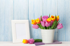 Fresh colorful tulips bouquet and photo frame. Fresh colorful tulip flowers bouquet and blank photo frame with copy space on shelf in front of wooden wall Royalty Free Stock Photo