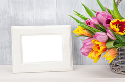 Fresh colorful tulips bouquet and photo frame. Fresh colorful tulip flowers bouquet and blank photo frame with copy space on shelf in front of wooden wall Stock Photography