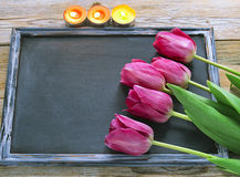 Fresh colorful tulips over wooden blackboard for copy space and. Candles on wooden planks royalty free stock photos