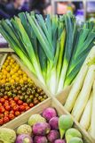 Fresh colorful vegetables on the counter of the store: leeks, cherry tomatoes, turnip.  Stock Photo