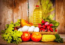 Fresh vegetables, eggs and a bottle of oil on a basket Royalty Free Stock Images