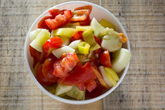 Fresh colorfull sallad. Cucumber and tomato sallad in the white dish on rustic wooden table royalty free stock images
