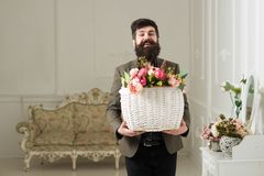 Fresh concept. Bearded man hold basket with fresh flowers. Man smile with fresh floral arrangement. Happy hipster with. Fresh bouquet royalty free stock photo