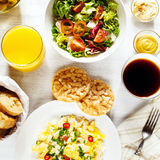 Fresh continental breakfast. Healthy food. Scrambled eggs, salad, cheese, prosciutto, coffee and juice. Concept of business or holiday breakfast. Top view Royalty Free Stock Image
