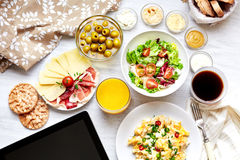 Fresh continental breakfast. Healthy food. Tablet, black screen. Scrambled eggs, salad, cheese, prosciutto, coffee and juice. Concept of business or holiday Royalty Free Stock Image