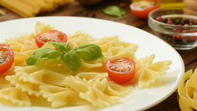 Fresh cooked farfalle with cut tomatoes and basil stock video