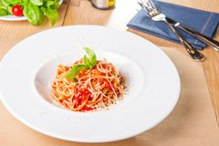 Fresh, cooked Italian spaghetti, pasta with marinara or tomato sauce decorated with basil on the white plate served on the wooden. Table with catlery. Selective stock photos