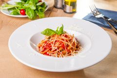 Fresh, cooked Italian spaghetti, pasta with marinara or tomato sauce decorated with basil on the white plate served on the wooden. Table with catlery. Selective royalty free stock photo