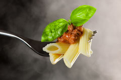 Fresh cooked pasta on fork with bolognese sauce and green basil Royalty Free Stock Photo