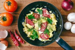 Fresh cooked scrambled eggs in pan with sausage, herbs. Tomato, chilli pepper, onion, mushroom on wooden board, top view Stock Images
