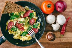 Fresh cooked scrambled eggs in pan with sausage and herbs. Tomato, onion, mushrooms on wooden board, top view Stock Image