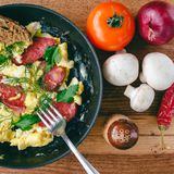 Fresh cooked scrambled eggs in pan with sausage and herbs. Tomato, onion, mushrooms on wooden board, top view Stock Photo