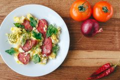 Fresh cooked scrambled eggs with sausage and herbs in white plate. Tomato, chilli pepper, onion on wooden board top view Royalty Free Stock Image