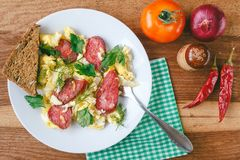 Fresh cooked scrambled eggs with sausage and herbs in white plate. Tomato, chilli pepper, onion on wooden board top view Royalty Free Stock Photography