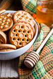Fresh cookies in a bowl, tablecloth and honey Royalty Free Stock Photography