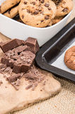 Fresh cookies on a griddle with chocolate pieces. And some Cookies in a bowl royalty free stock photos