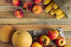 Fresh corn, apples, peaches and melons on rustic wooden background. Warm still life with free space for Your text. stock photo