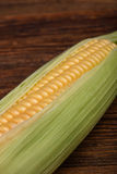 Fresh corn cob maize on the wooden table, top view closeup Royalty Free Stock Photography