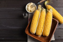 Fresh corn on the cob with salt and butter on wooden table, closeup, top view. Dark background with copy space Stock Image