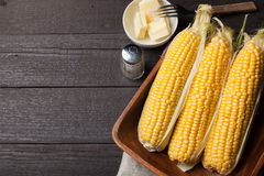 Fresh corn on the cob with salt and butter on wooden table, closeup, top view. Dark background with copy space Stock Photos