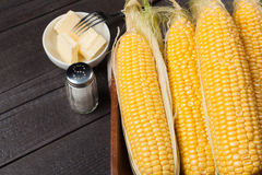 Fresh corn on the cob with salt and butter on wooden table, closeup, top view. Dark background with copy space Stock Photo