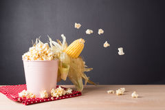 Fresh corn on cob on wooden table, closeup. Fresh corn on cob and popcorn on wooden table dark background, closeup, Ear of corn stock photos