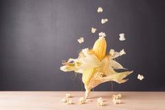 Fresh corn on cob on wooden table, closeup. Fresh corn on cob and popcorn on wooden table dark background, closeup, Ear of corn stock images