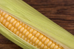 Fresh corn cob on the wooden table closeup, top view Stock Image