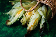 Fresh corn on cobs on green wooden table Stock Photo