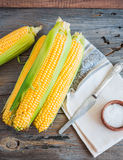Fresh corn on cobs on a wooden surface, whole plant foods, top v Royalty Free Stock Photos