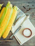 Fresh corn on cobs on a wooden surface, whole plant foods, top v Stock Images